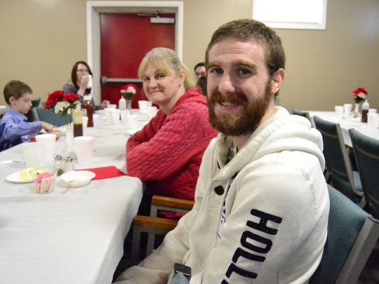 Hunter McGraw, 23, from Conklin who is currently in the Army Reserves enjoys a free breakfast with his mother Penny McGraw at the Christian Church of Fellowship in Kirkwood Sunday
