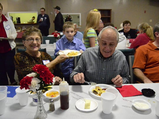 Mike Stebela, 65, and his wife Jane Stebela, 68, from the Town of Chenango being served breakfast by Caleb Cunningham, 8, at the Christian Church of Fellowship's annual free breakfast for Veterans Sunday in Kirkwood