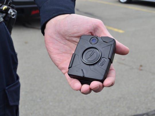 Binghamton Patrolman Brad Kaczynski holds a body camera during a media demonstration in 2015.