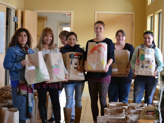 A group of volunteers from the German Helping Hands and Casa Hogar de Bethel Orphanage stand with Christmas gift bags they've prepared for orphans in Juarez.