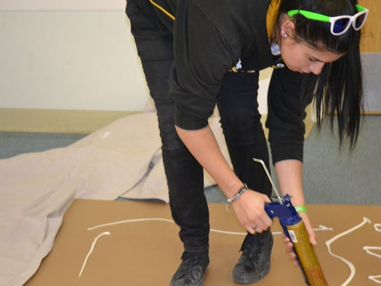 A volunteer helps install long white boards at the Alamogordo High School Administration Building F where robotics teams build and design their robots.