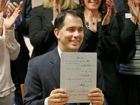 Wisconsin Gov. Scott Walker shows Senate Bill 293 after he signed it into law Friday at the Bellin Health Psychiatric Center in Allouez.