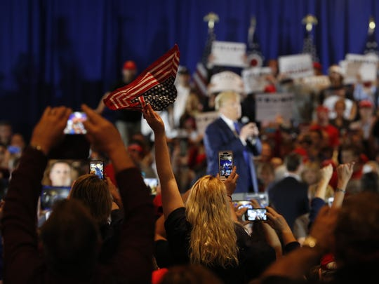 An American flag waves in the foreground as Donald Trump addressed the gathered crowd during his West Chester campaign stop Sunday afternoon.