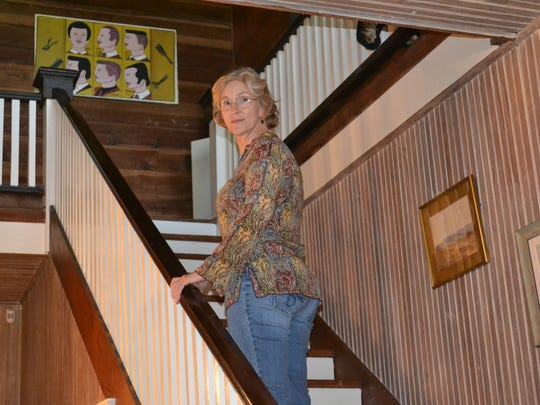 Sara Fuhrer pauses on the stairs of her 103-year-old house called Chickama. She is attempting to get the house, which is located near Lecompte, added to the National Register of Historic Places.