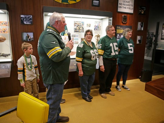 Members of the Purinton family stand in the replica of Vince Lombardi's office at the Green Bay Packers Hall of Fame as Dick Purinton, left, talks about the history behind a 1961 championship team autographed football they donated April 8,  2016.