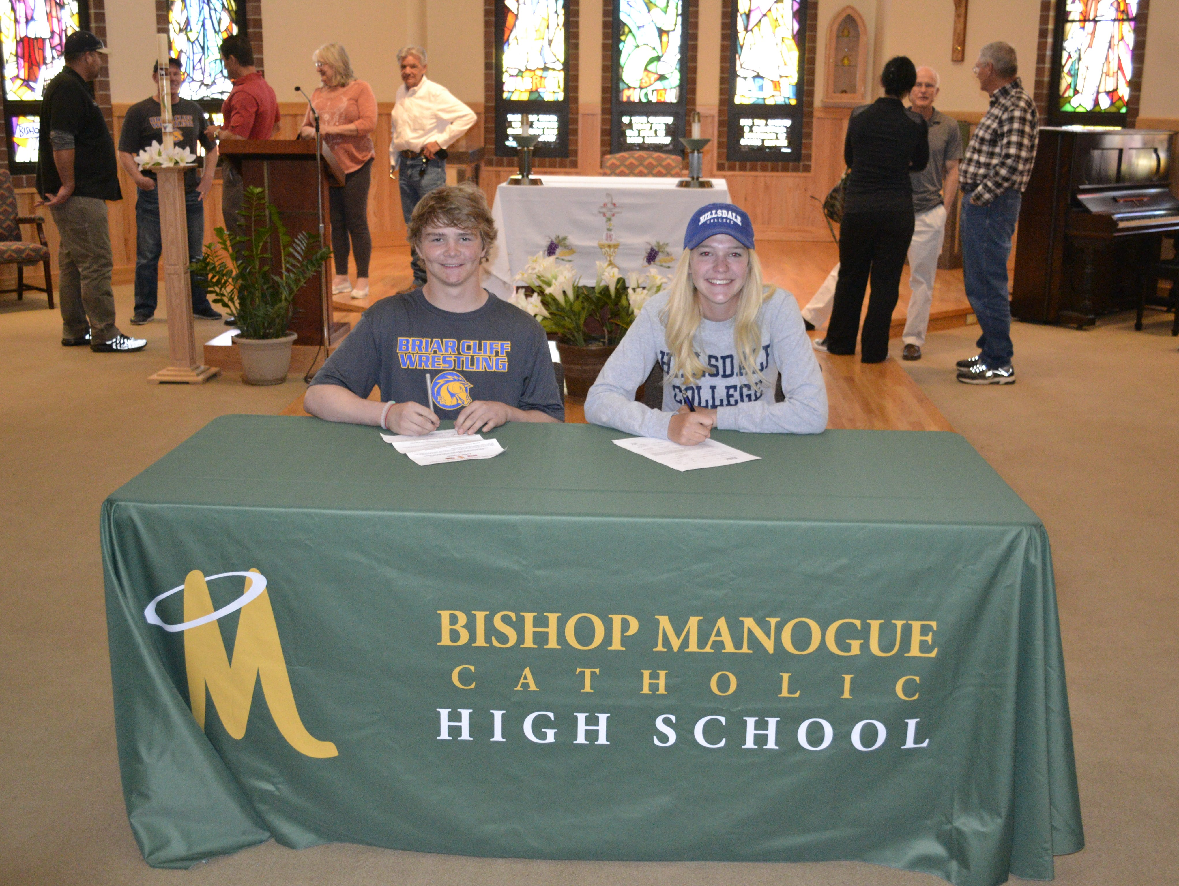 Bishop Manogue athletes Bailey Bright, left, and Alyssa Viola, sign their letters of intent Monday at the school.