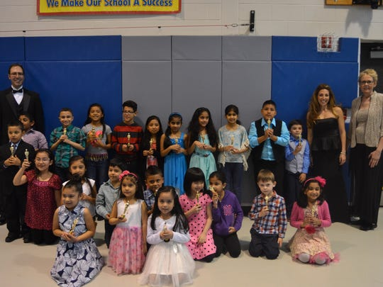 Children enrolled in the K-3 English as a Second Language program at the Alan B. Shepard Elementary School  pose for a photograph with their principal, Joseph Marinzoli (far left) and their teachers Kaia Karmyn and Veronica O'Brien (far right) at the conclusion of the premiere of the 2015-2016 edition of Shark News 12.