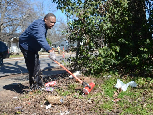 ANI Garbage on streets Alexandria City Councilman Roosevelt Johnson looks at the trash littering the bus stop at the corner of Lee and Dallas Streets Friday, Feb. 6, 2015. He said there is an effort to try to get people to quit littering in the area.-Melin