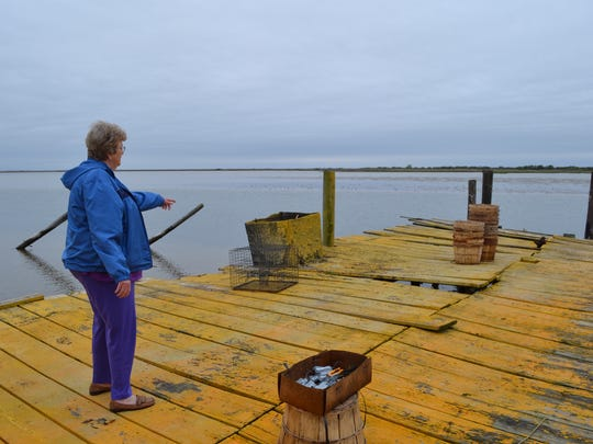 Maxine Landon of Rhodes Point, Smith Island, stands on her family's dock that has been battered by Hurricane Sandy and other storms.