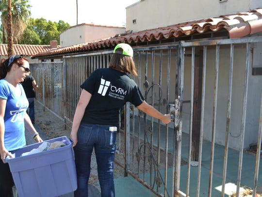 Heather Oster, right, of Health to Hope Clinics, checks the lock on an abandoned church in Palm Springs Thursday, June 23, 2016. Oster and volunteer Marnie Mandel, left, carry a container full of water to pass out to the needy.