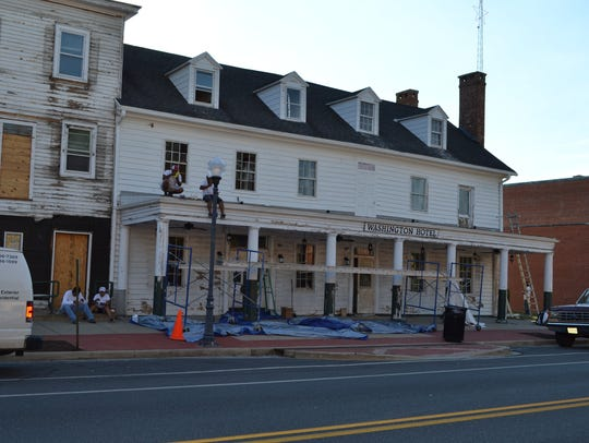 Contractors do exterior work on the old Washington