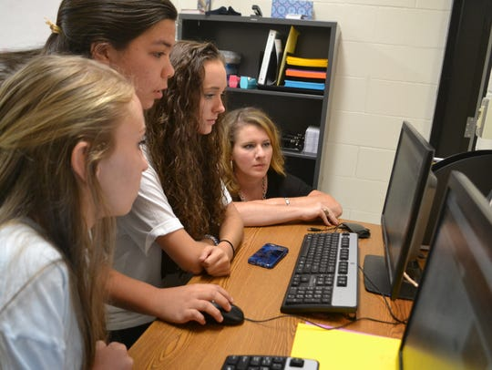 Amy Jennings (far right) crouches down checking yearbook