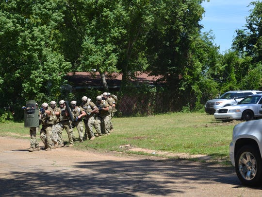 A tactical team begins its advance on a house on Greenway Drive as part of a training exercise Wednesday.