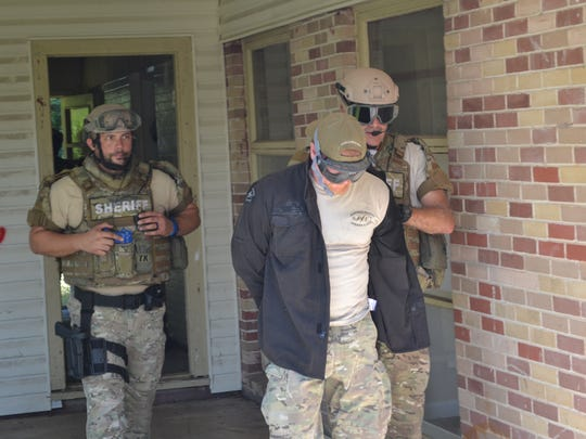 Rapides Parish Sheriff's Office tactical team members bring out the captured suspect during a training exercise Wednesday at a vacant house on Greenway Drive in Greenway Park subdivision.