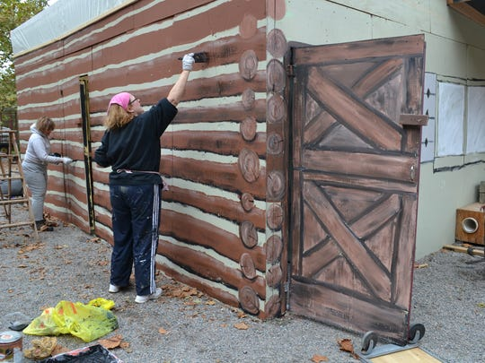 Volunteers work on sets for the Red Mill Haunted Village.