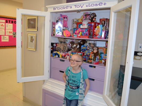 Brooke Mulford poses in front of Brooke's Toy Closet