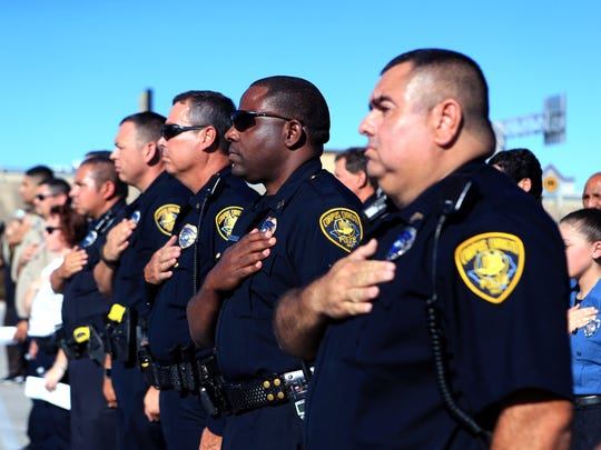 Rachel Denny Clow/Caller-TimesCorpus Christi Police Department officers hold their hands over their hearts as the national anthem is performed during the National Night Out Kick-off at the Sam's Club parking lot on Tuesday, October 4, 2016. Neighborhoods throughout the city participated in the national event.