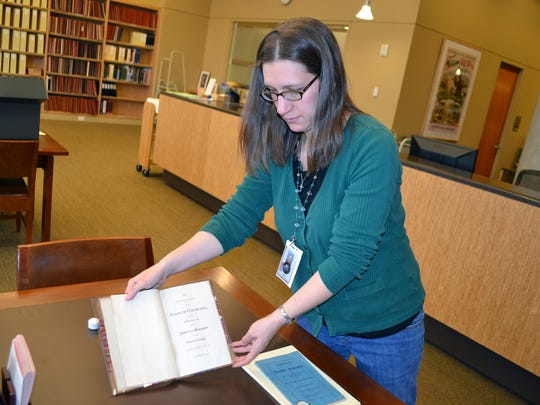 In this Nov. 12, 2016 photo, reference librarian Sarah Gilmor holds an 1876 copy of the Colorado Constitution which contains an exception under which slavery could be used as punishment for a crime, at the Stephen H. Hart Library & Research Center in Denver. Colorado's voters were asked to eliminate an archaic and offensive reference to slavery as a punishment for a crime in the state Constitution. But a week after the vote, the poorly-written amendment is on the cusp of failing, and a lack of clarity from lawmakers may be to blame. (AP Photo/P. Solomon Banda)