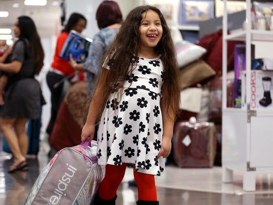 Leila Boudif, 6, carries a comforter through JCPenney