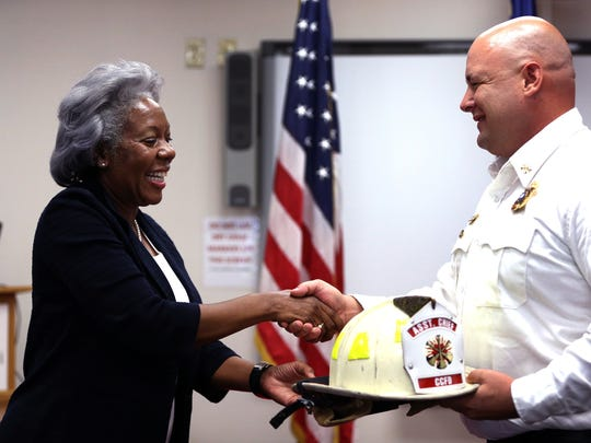 City Manager Margie Rose presents a helmet to Kenneth