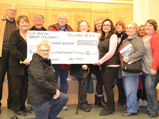 Clockwise from bottom, North Mason Cancer Crusaders members Mary Marsh, John Wiechert, Shelly DeBritz, Rodger DeBritz, Don LePere, Linnie Griffin, Tina Haymaker, Linda Casteel, Linda Maynard, Kaye Massie, Rebecca Miller and Paula Young visited the Fred Hutchinson Cancer Research Center on Dec. 14. The North Mason Cancer Crusaders donated nearly $14,000 this year to the Fred Hutchinson Cancer Research Center primarily through funds raised from the group's September Jail and Bail fundraiser.