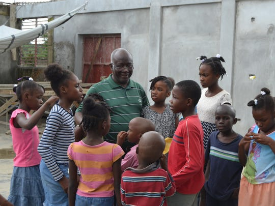 Children gather around Father Andre Sylvestre at the orphanage in Haiti.