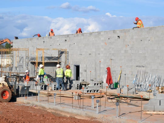 Construction crews work Friday afternoon on building the walls for the new eight-classroom wing at Concrete Primary School in Williamston.