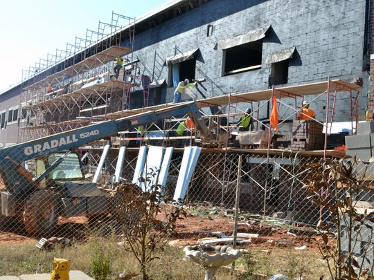 Construction crews lay bricks on the outside of new 26-classroom wing at Robert Anderson Middle School on Friday afternoon.