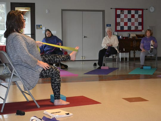 Instructor Julie Forville leads a pose in a chair yoga class at the HUB Center for Seniors in Belfair. Forville is a certified SilverSneakers instructor, teaching classes at the senior center and at the Form Fit 24-hour gym in Belfair.