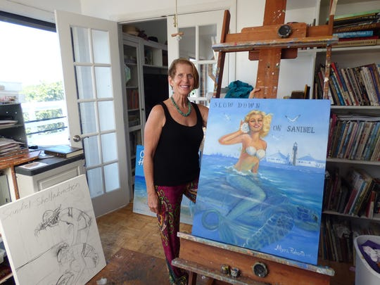 Myra Roberts with a painting of hers at her studio.