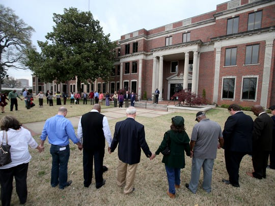 Concerned citizens join hands in prayer outside Shelby County Juvenile Courthouse to pray for juvenile offenders, juvenile providers and the people and the families that they serve.