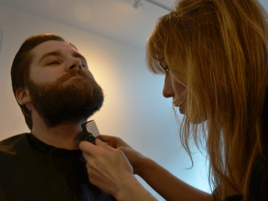 Chaus Davids, left, keeps his chin up as Dana Schlosser trims his beard. Schlosser has opened a mens and women's barbershop called Meta Hair Studio.