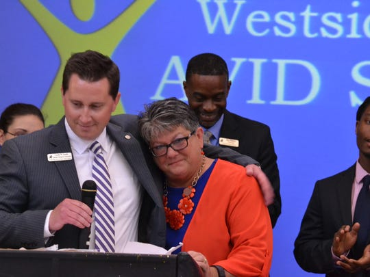 Westside Assistant Principal Curtis Smith hugs Associate Principal Kathy Dobbins as her students and fellow co workers applaud her work at the AVID College Signing Day Friday morning.