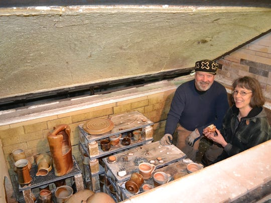 Husband and wife potters John Benn and Colleen Gallagher of Harstine Island sit in one of the wood-fired kilns they built themselves in a workshop studio outside their home in 2013. Their studio will be open to the public during the Harstine Island Art Studio Tour Memorial Day weekend.
