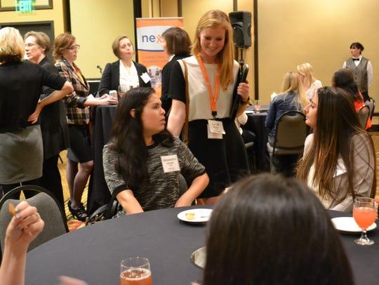 Women talk at a Nexxus meeting.
