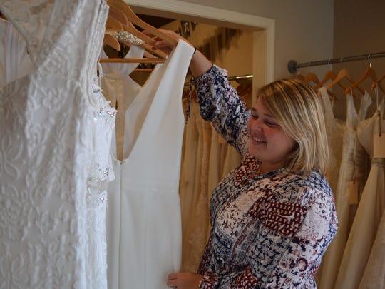Julie Snowden, manager of Dryden Dress Co., hangs wedding