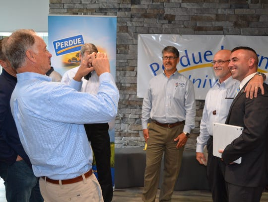 Jim Perdue, left, chairman of Perdue Farms, takes a