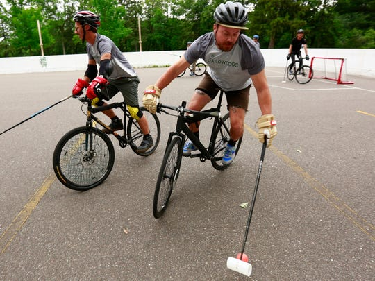 Hardwoods member Seth Carlson, right, maintains control of the ball during a bike polo practice Thursday, June 29, 2017, at the Riverside Park in Wausau.