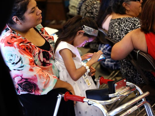 Crystal Levine sits with her daughter, Alyssa Hernandez, 8, as she and her twin sister compete in the Miss Magnificent Pageant, a pageant for individuals with special needs, on Saturday, May 28, 2016 at Recio's Smokehouse and Catering.