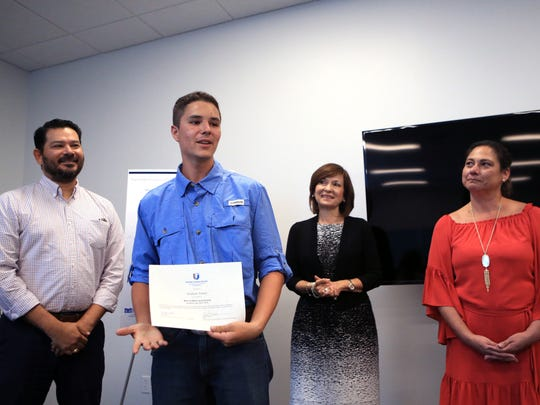 Christian Toren, a recipient of the Mano a Mano scholarship, speaks during a scholarship reception as United Corpus Christi Chamber of Commerce Foundation board member Eric Villarreal (from left), chairwoman Carmen Arias and Executive Director Yvette Lara listen during the event at the Corpus Christi Regional Transportation Authority on Wednesday, August 2, 2017.