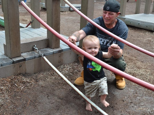 Robert Ray plays with his son, Robert, 1, at Ben's Red Swings on Monday, Aug. 14.