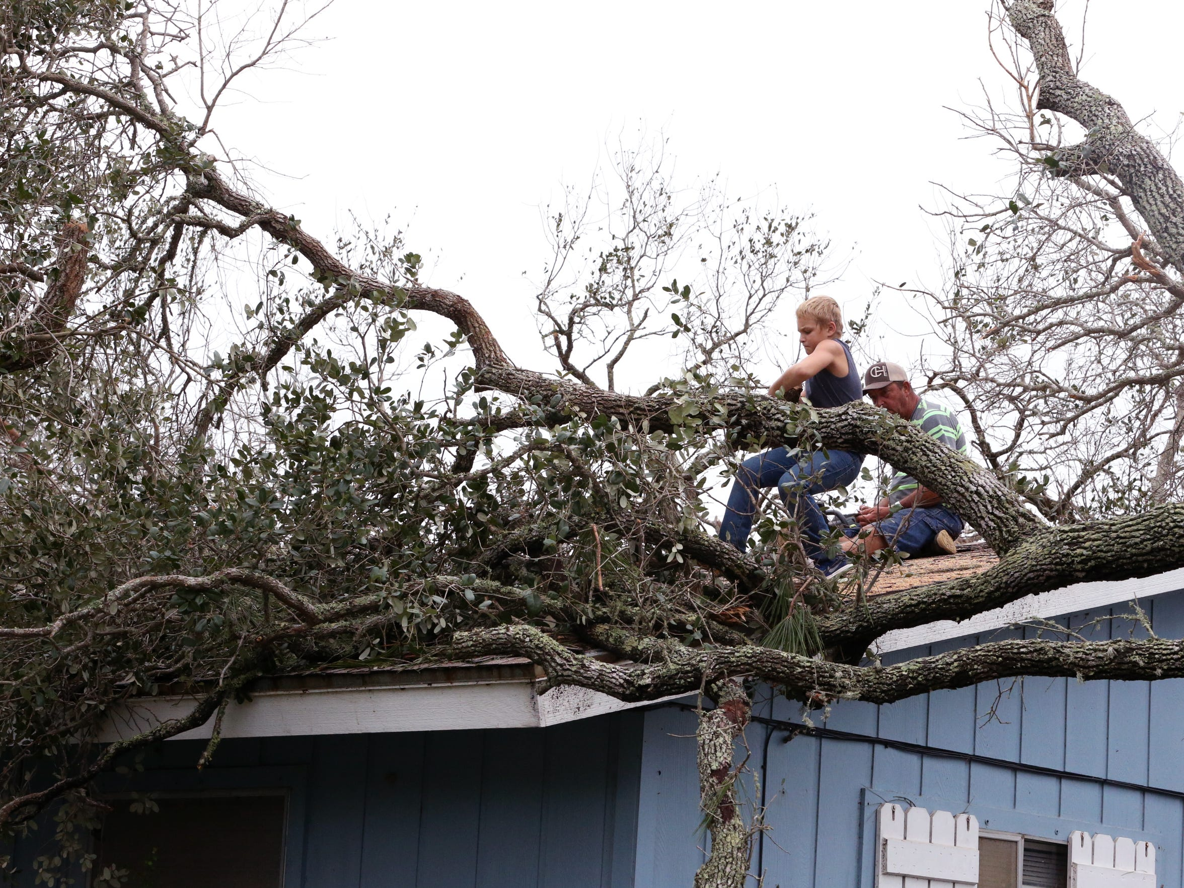 Cainan Ayers, 11, helps his grandfather, Cliffton Padier, remove a tree from their roof in Rockport, TX, on Sunday, August 27, 2017, two days after Hurricane Harvey devastated the Coastal city.