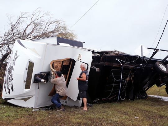 Volunteer Caleb Carr (left) helps Les Currie try to get into his trailer on Monday, August 28, 2017 off FM 1781 in Aransas County, TX in an damaged by Hurricane Harvey. Currie evacuated quickly and didn't have a chance to gather his paperwork.