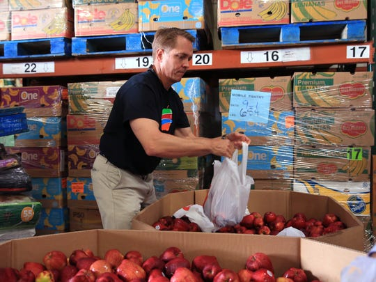 Brantley White, board member of the Coastal Bend Food Bank bags apples following the unveiling of the new namefor the food bank on Wednesday, September 6, 2017. The name greater reflects the community they serve, which is several counties.
