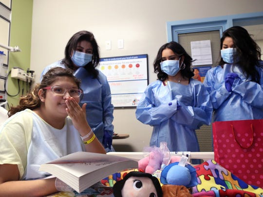 Aliza Luna Pena (from left), 14, gets a visit from