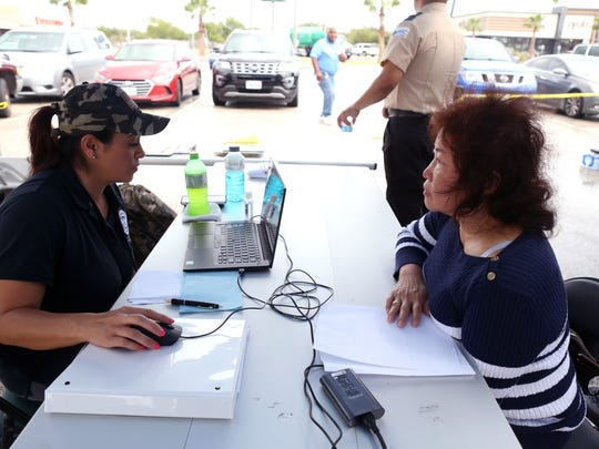 Esperanza Espinosa (left), an applicant services specialist with FEMA, assists Hetty Long at a FEMA site at La Palmera mall on Tuesday, Oct. 2, 2017.