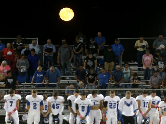 A full moon lingers above Richland Springs Coyotes and fans during a moment of prayer at Friday night's game against the Sterling City Eagles, Oct. 6, 2017.
