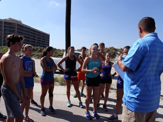 Steve Reaves talks with members of his cross country team from Port Aransas High School before they run along the beach on Wednesday, October 18, 2017.