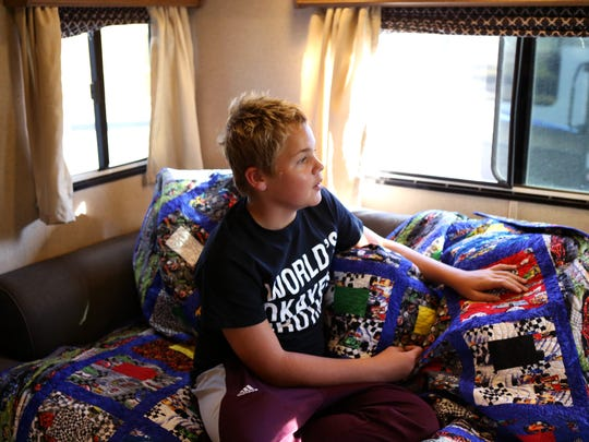 Casey McGrady, 12, looks out the window from the living area in his family's new home Tuesday, Oct. 24, 2017. His family received an RV through the Homes for Displaced Marlins program. He sleeps on the couch, two of his brothers share a room and another brother has his own room. The family, whose children attend Port Aransas ISD, was displaced by Hurricane Harvey.