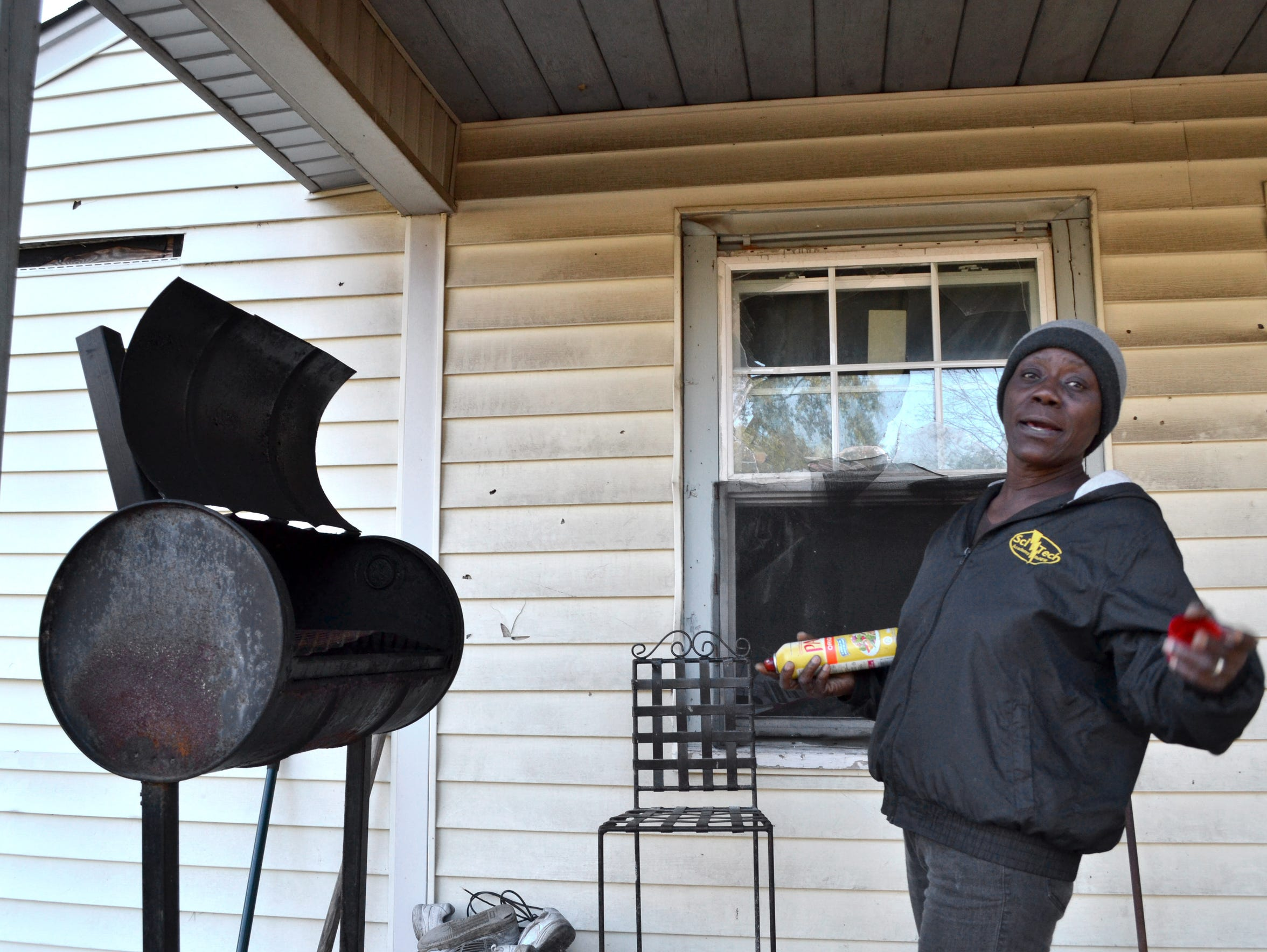 Patricia Aaron stands by the grill outside her house, down the street from where she's currently living. The house needs work, which she said she expects she can afford to do next year.